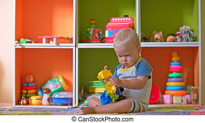 Toddler boy plays with toys in child room