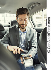 Man paying the taxi with the mobile phone NFC technology