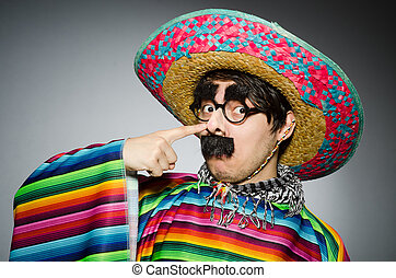 Man in vivid mexican poncho against gray