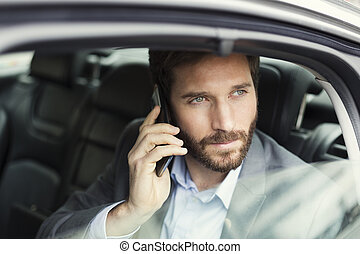 Casual business man on mobile phone in rear of the car -...