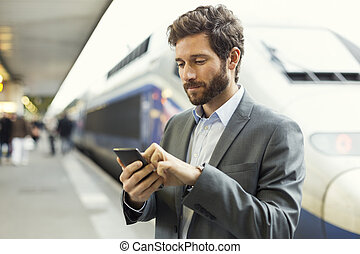 Man on platform station Typing text message on mobile phone