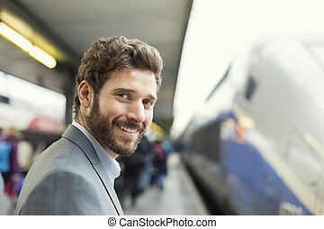 Portrait of cheerful man on platform station Looking camera...