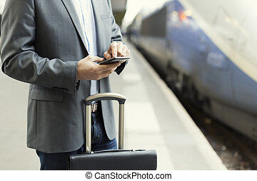Man on the platform station. Typing text message on cell...