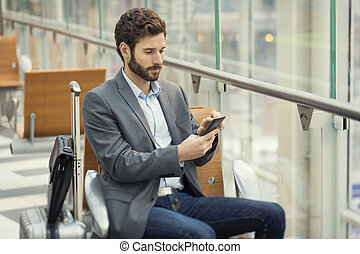 Man in the hall airport. Typing text message on mobile phone