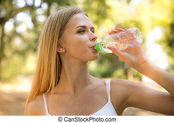 Woman dirnking water outdoors - Portrait of a beautiful...