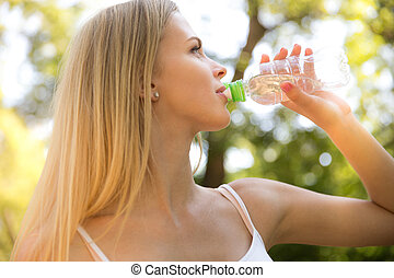 Woman dirnking water outdoors - Portrait of a young woman...