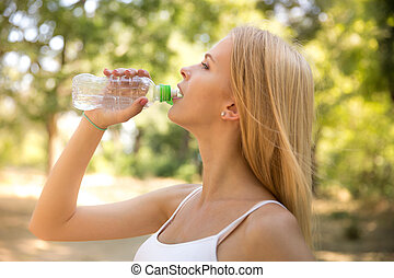 Woman drinking water in park - Portrait of attractive woman...
