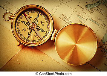 Antique brass compass over old map...