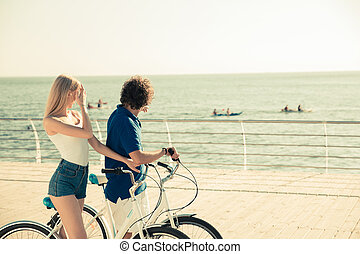 Man and woman on bicycle looking at sea