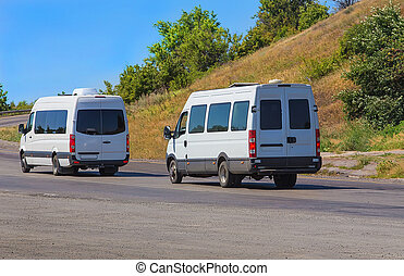 minibuses go on the twisting road - white minibuses go on...