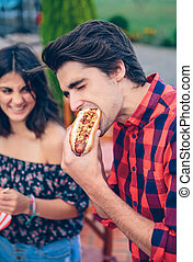 Young man eating hot dog and woman laughing in background -...