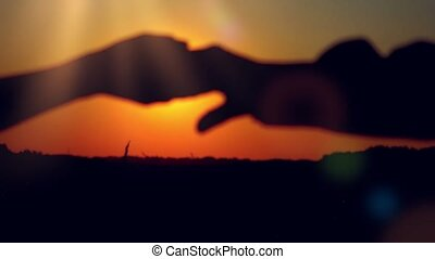 Silhouette of happy couple join hands runs across the field...