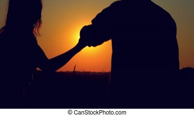 Silhouette of  happy couple join hands runs across the field in sunset light, lifestyle - happiness