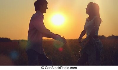 Couple hugging whirl in happiness on the field at sunset