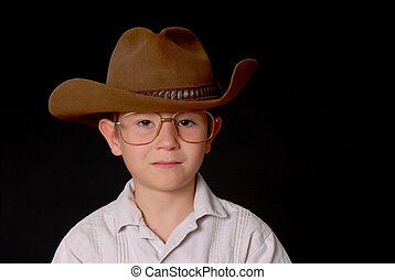 Young Cowboy - Young boy wearing a cowboy hat isolated on...