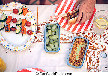 Male hand holding hot dog on red striped plate - Closeup of...