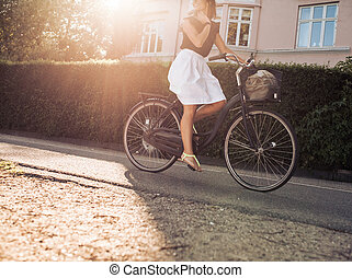 Woman riding bicycle along the street - Cropped shot of...