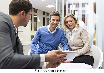 Young couple meeting real-estate showing a house project on...