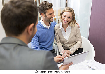 Young couple meeting real-estate showing a investment...