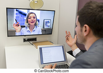 Businessman on video conference with her colleague in office...