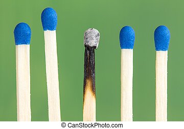 Row of match sticks on  green background