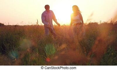 Fashionable happy couple runs across the field in sunset...