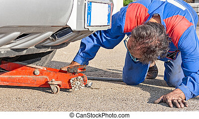 mechanician work under a car