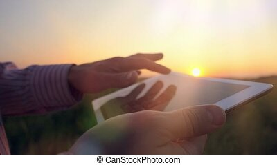 Young businessman working outdoors with tablet at sunset in the field