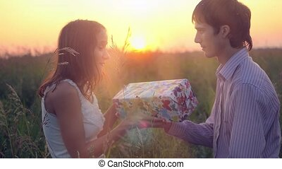 Man giving to his woman a gift box, smiling , hugging. Happy...