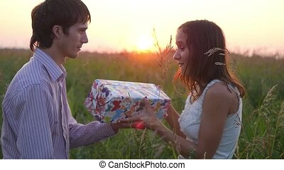 Man giving to his woman a gift box, smiling , hugging. Happy couple in love outdoors in the sunlight at sunset. Love concept.