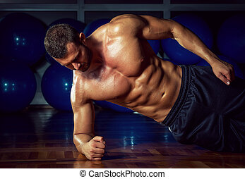 Side plank exercise - Man doing side plank exercise in gym