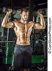 Man doing bicep curls - Young adult man doing bicep curls in...