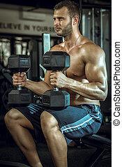 Man doing shoulder press - Young adult bodybuilder doing...