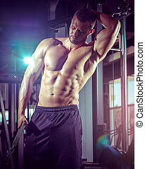 Man doing cable fly in gym - Young adult man doing cable fly...