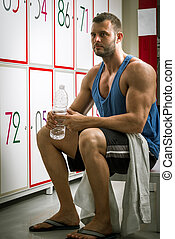 Man drinking water in locker room - Young adult tired man...