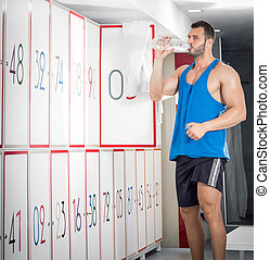 Young adult man drinking water in locker room - Young fit...