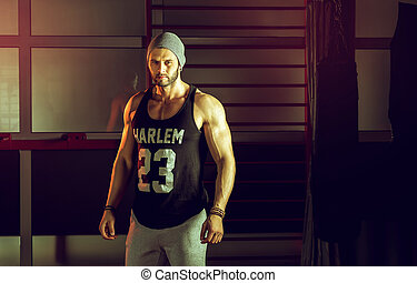 Man posing in gym - Young stylish adult man posing in gym