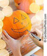 close up of woman with pumpkins at home - holidays,...
