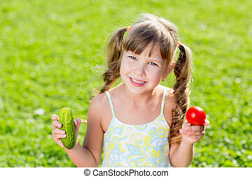 Happy child on summer grass background with healthy vegetables in hands.
