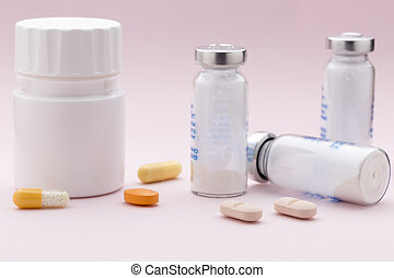 The set of medicine bottles, colorful pills and injection syringe