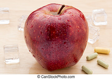 Colorful medicine capsules and red apple