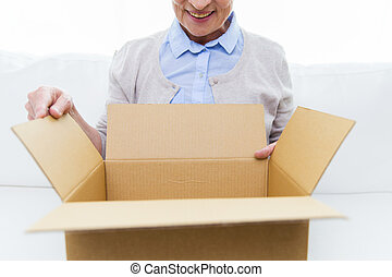 close up of senior woman with parcel box at home - age,...