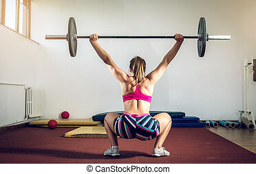 Girl doing squats with weight - Young adult girl doing heavy...