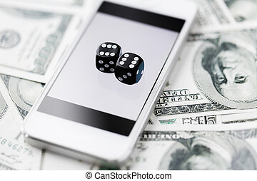 close up of dice with smart phone and cash money - casino,...