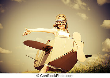 dream flight - Little dreamer girl playing with a cardboard...