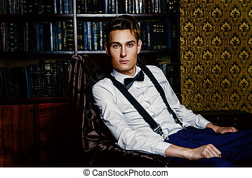 thoughts by a fireplace - Elegant handsome young man sitting...