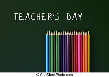 coloured pencils and text teachers day written in a green...