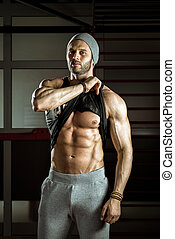 Man posing in gym - Young stylish adult man posing in gym...