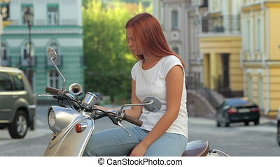 Girl sitting on scooter in european city - Young cheerful...