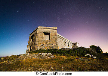 Ruins of a former military building on a night photography with the moonlight.